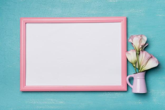 Weißer leerer bilderrahmen mit rosa rand und vase auf blauem hintergrund