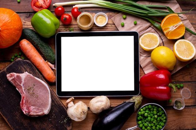 Weißer leerer bildschirm der elektronischen tablette gemäßigt mit fleisch und verschiedenem gemüse auf einem hölzernen hintergrund