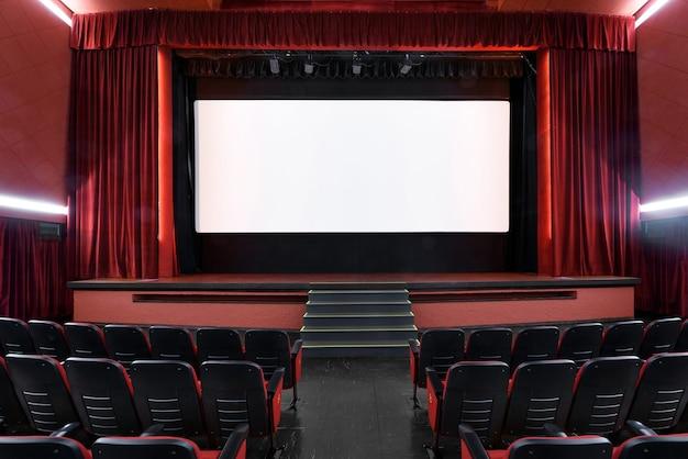 Weißer leerer bildschirm im leeren kino mit sitzreihen und rotem interieur