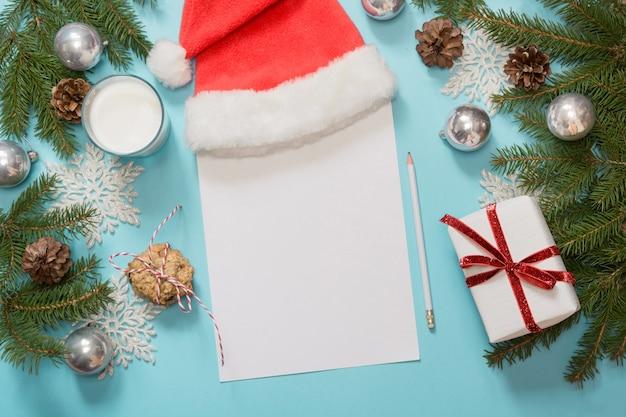 Weißer leerer brief für den weihnachtsmann mit milch, keksen, tannenzweigen, tannenzapfen und weihnachtskugeln