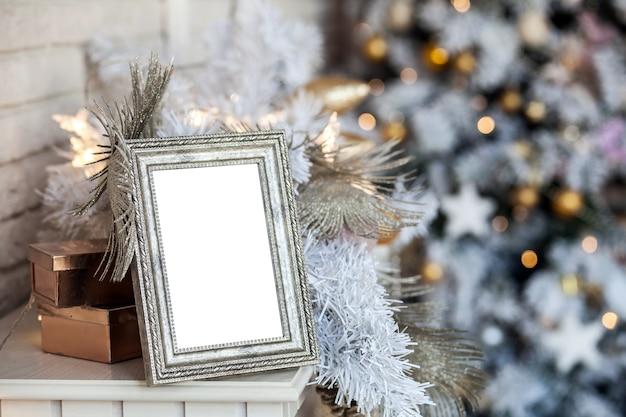 Weißer leerer fotorahmen auf dem kamin. weihnachtsweißes interieur mit bokeh-defokussierungseffekt