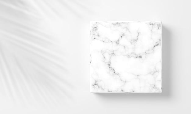 Weißer leerer quadratischer marmor in weißem hintergrund mit dekoration durch schattenblätter