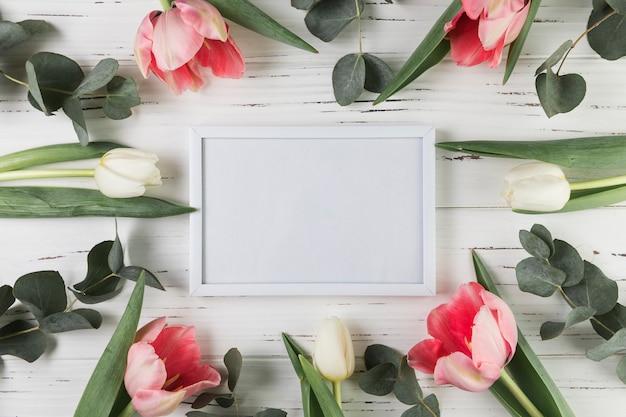 Weißer leerer rahmen umgeben mit weißen und rosa tulpen auf hölzernem schreibtisch
