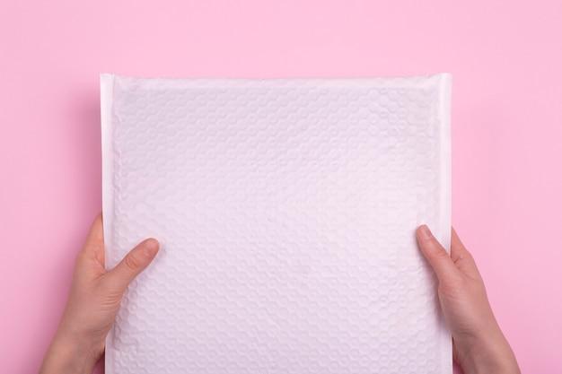Weißer leerer umschlag mit postpaket in den händen auf einem rosa hintergrund. postindustrie und frachtzustellung.