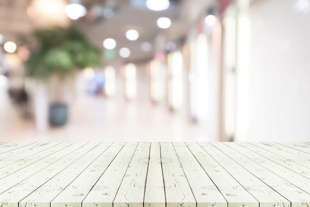 Weißer leerer weißer holztisch der perspektive über unscharfem einkaufszentrumhintergrund