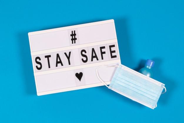 Weißer leuchtkasten mit nachricht stay safe, medizinische schutzmaske und handgel auf hellblau