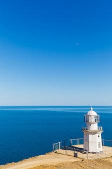 Weißer leuchtturm auf einem hintergrund von blauem meer
