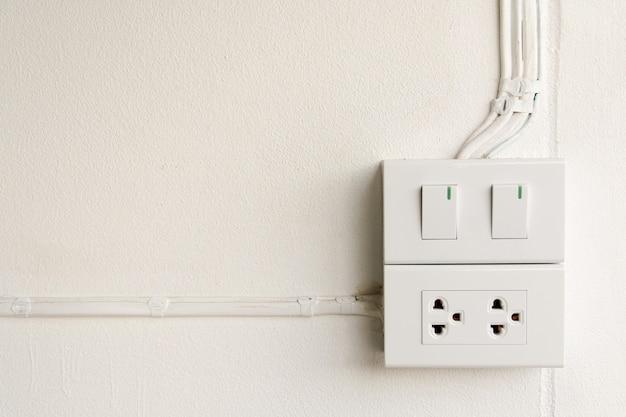 Weißer lichtschalter und steckdose an der wand schalten die lichter ein oder aus, kopieren platz für text