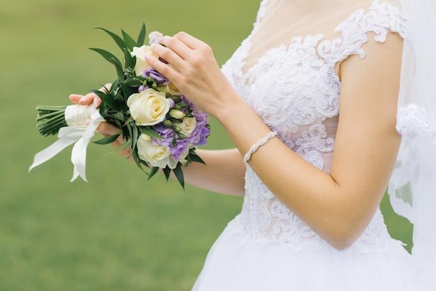 Weißer lila hochzeitsblumenstrauß schön in den händen der braut