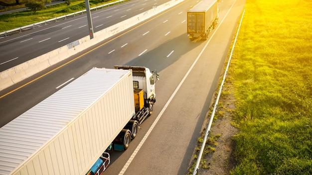 Weißer lkw auf autobahn mit container mit schönem sonnenlicht