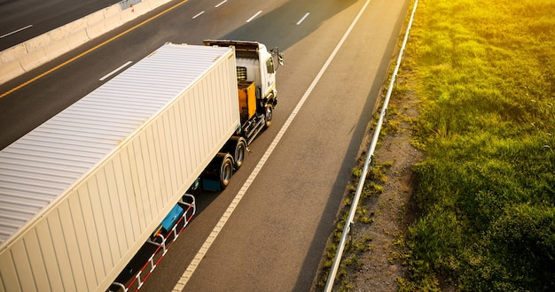 Weißer lkw auf der autobahn mit container, transportkonzept., import, export logistik industrie transport landverkehr auf der schnellstraße. bewegung zu weichzeichner verwischt