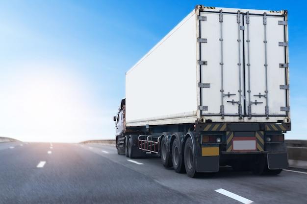 Weißer lkw auf landstraße straße mit behälter. landtransport transportieren