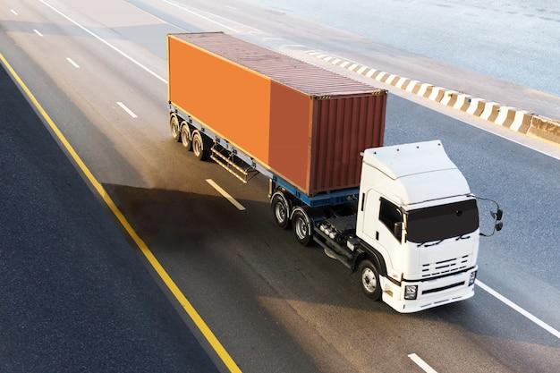 Weißer lkw auf landstraße straße mit rotem behälter, logistischer transport auf der asphaltautobahn