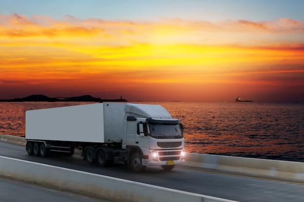 Weißer lkw auf landstraßenstraße mit behälter, import, logistischer industrieller transport des exports