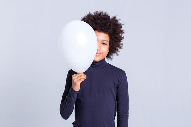 Weißer luftballon. hübscher junger mann mit afro-frisur, der die hälfte seines gesichts mit einem ballon schließt, während er einen blauen rollkragenpullover trägt