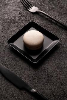 Weißer makronenkuchen in einem quadratischen teller. stilvolles minimalistisches nahaufnahmefoto. schwarze gabel und löffel. grafisches lebensmittelfoto in dunklen farben, vertikale anordnung.