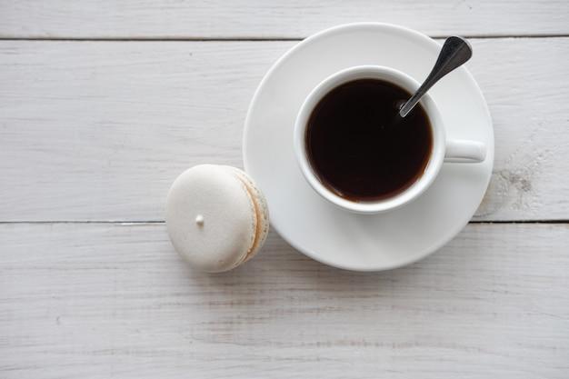 Weißer makronenkuchen und weiße kaffeetasse auf weißem holztisch