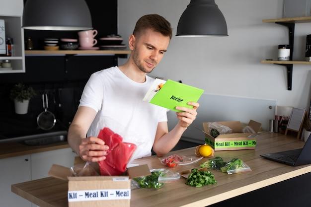 Weißer mann auspacken online home food delivery. box mit verpacktem thunfisch, garnelen in der küche. lieferservice für lebensmittel.