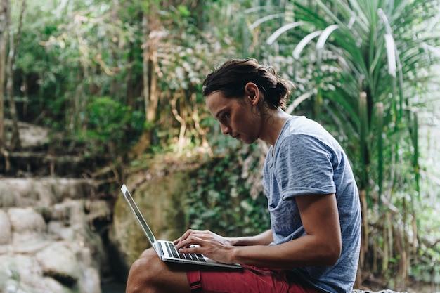 Weißer mann, der computerlaptop am wasserfall verwendet