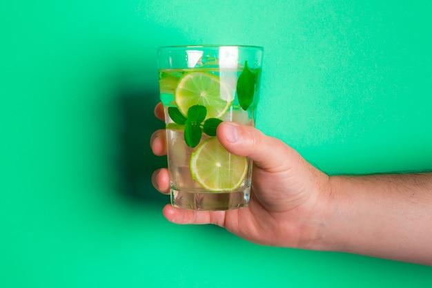 Weißer mann, der ein glas frische limonade mit zitronenstücken und basilikum auf dem grün hält