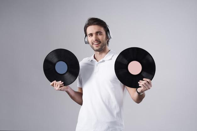Weißer mann, der mit den vinylaufzeichnungen lokalisiert aufwirft.