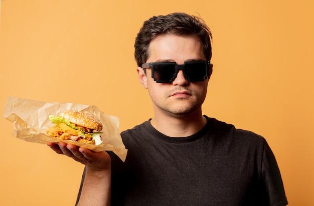 Weißer mann im schwarzen t-shirt mit burger auf gelber wand