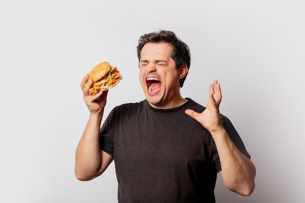 Weißer mann im schwarzen t-shirt mit burger auf weißer wand