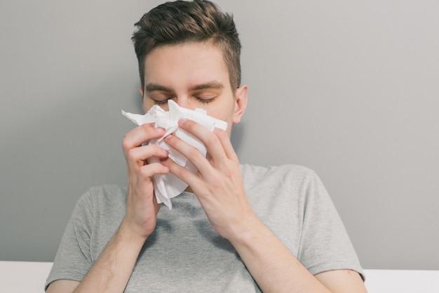 Weißer mann wird krank und putzt sich die nase in eine weiße serviette