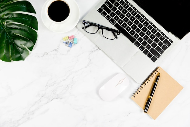 Weißer marmorschreibtisch mit leerem notizbuch und anderem büroartikel