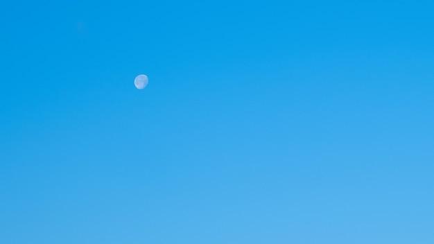 Weißer mond und blauer morgenhimmel.
