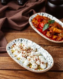 Weißer mozarella-käse der draufsicht mit fleischschale auf dem braunen hölzernen schreibtischmahlzeitlebensmittelfleisch