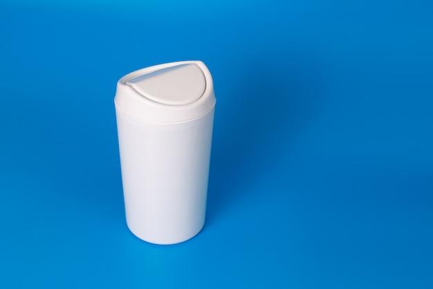 Weißer mülleimer des kleinen tisches auf blau