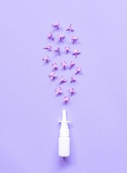 Weißer nasenspraybehälter, salzwasserlösung für nasenstauungsbehandlung und allergie, flache lage, gesundes konzept, lila blumen