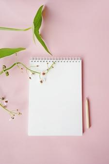 Weißer notizblock auf rosa hintergrund mit grünen blättern.