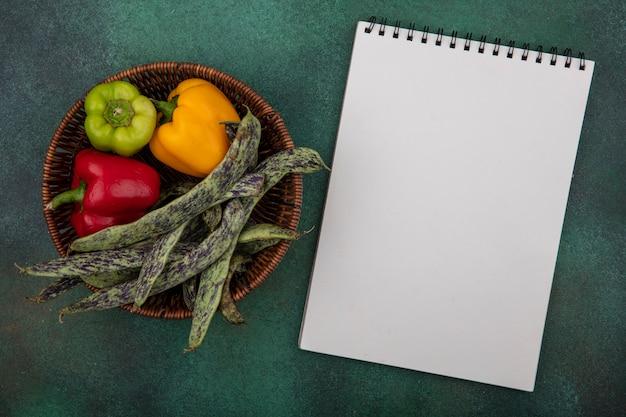 Weißer notizblock des kopierraums der draufsicht mit grünen bohnen und paprika in einem korb auf grünem hintergrund