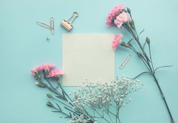 Weißer papierraum mit blume auf pastellfarbenem hintergrund.