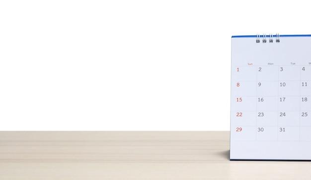 Weißer papierschreibtischkalender auf hölzerner tischplatte lokalisiert auf weißem hintergrund