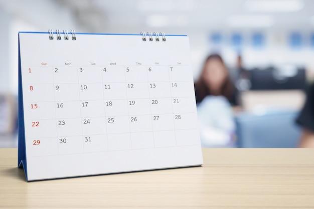 Weißer papierschreibtischkalender auf holztisch