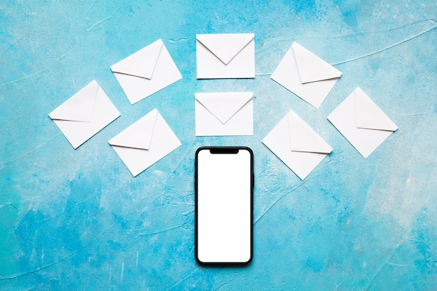 Weißer papierumschlag der mitteilungsikonen über mobiltelefon auf blauem strukturiertem hintergrund