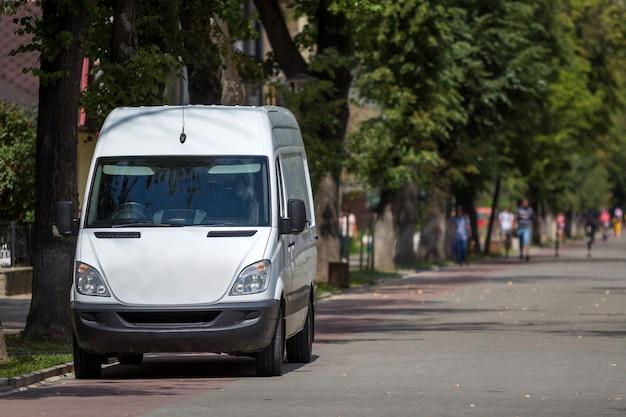 Weißer passagier mittelgroßer kommerzieller deutscher luxus-kleinbus, geparkt auf stadtstraße mit verschwommenen silhouetten von fußgängern und fahrendem auto unter grünen bäumen.