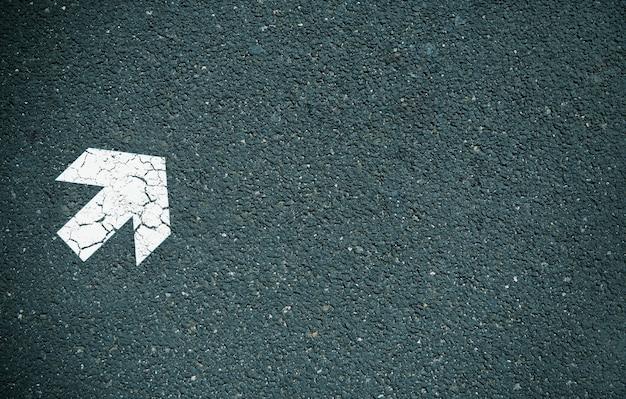 Weißer pfeil auf asphalt gemalt