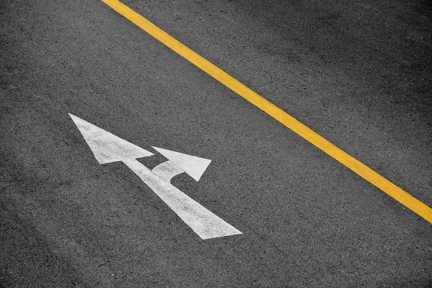 Weißer pfeil auf asphaltstraße gemalt (geradeaus fahren und rechts abbiegen)