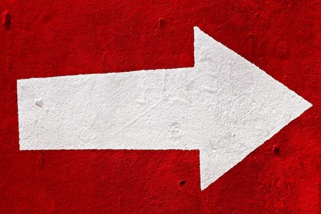 Weißer pfeil auf dem roten beton.