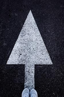 Weißer pfeil nach vorne auf dem asphalt und füße in weißen turnschuhen.