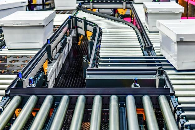 Weißer plastikkasten auf förderband pakettransportsystem
