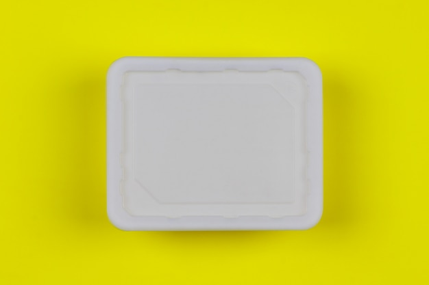 Weißer plastikkasten des modells auf draufsicht des gelben hintergrundes