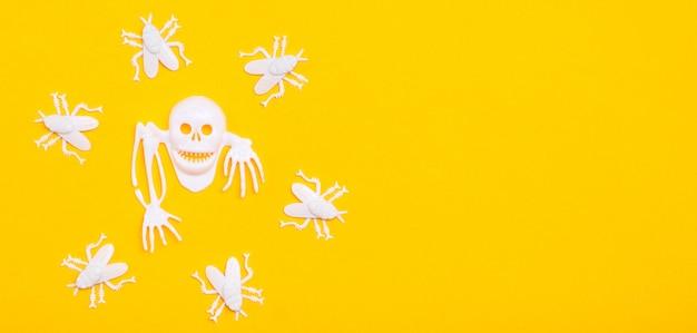 Weißer plastikschädel mit den knochen umgeben durch weiße plastikfliegen auf einem gelben papphintergrund.