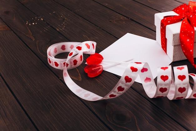Weißer präsentkarton mit rotem band steht auf leerer karte auf holztisch