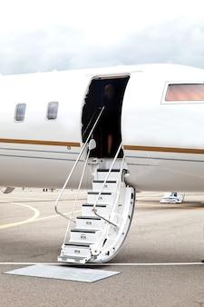 Weißer privatgeschäftsjet und offene leiter am flughafen