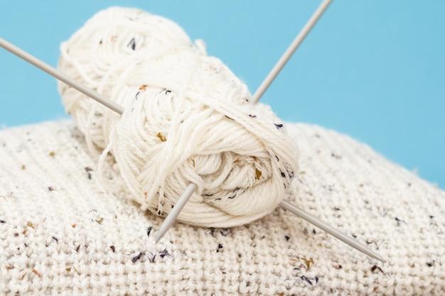 Weißer pullover und garnknäuel mit metallstricknadeln auf blauem grund. strickkonzept. geringe schärfentiefe.